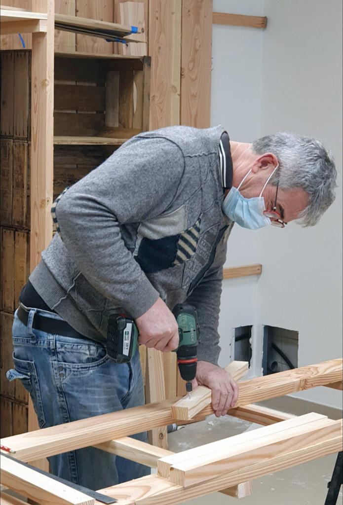 Bénévole en train de préparer les étagères des Halles de Châtelais